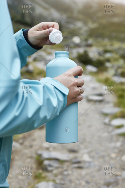 Female hiker opening drinks flask on dirt track, cropped