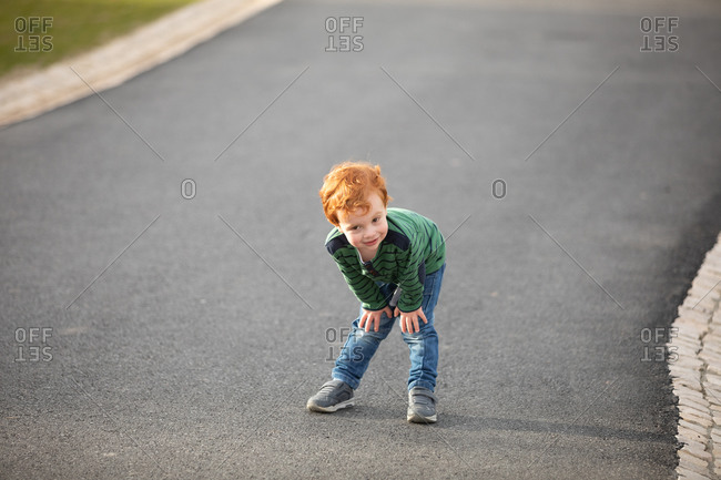 Boy stopping to rest on road