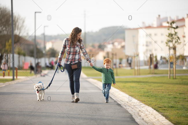 Mother and son walking with pet puppy on quiet road