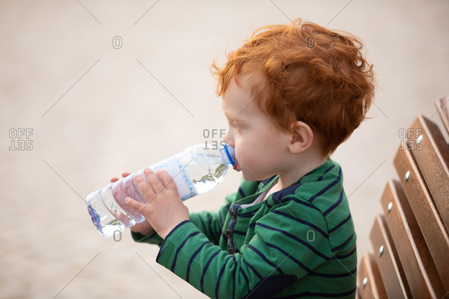Boy drinking water on park bench