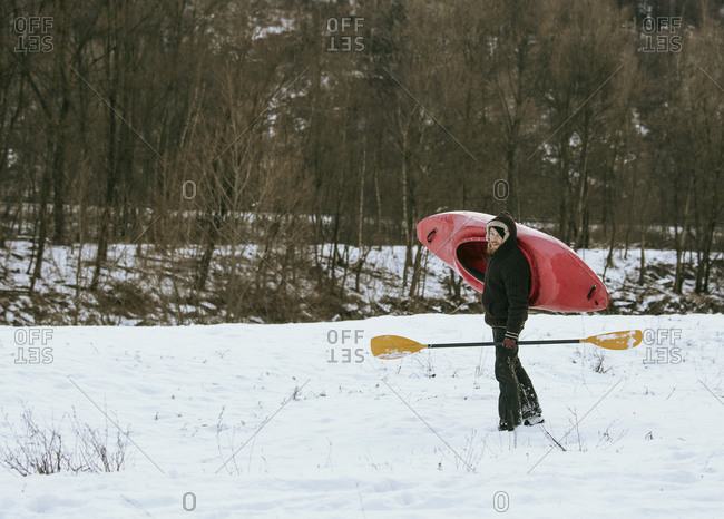 Male kayaker carrying kayak over his shoulder in snow, Domodossola, Piemonte, Italy