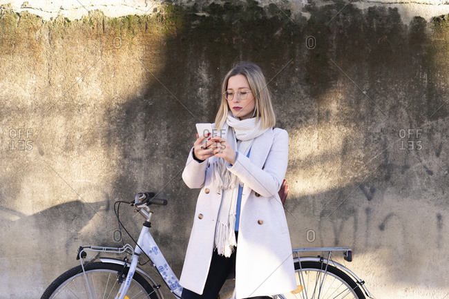 Female higher education student with bicycle looking at smartphone