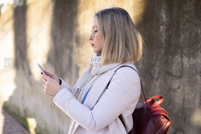 Female higher education student by sunlit wall looking at smartphone