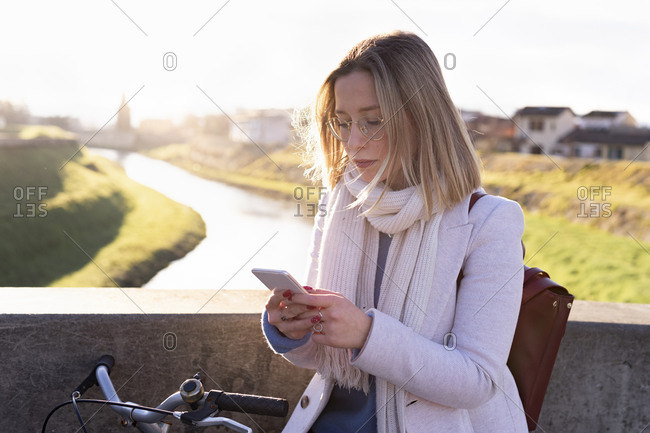 Female higher education student on river bridge looking at smartphone, Florence, Italy