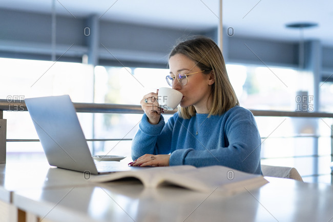 Female higher education student looking at laptop and drinking coffee in university cafe