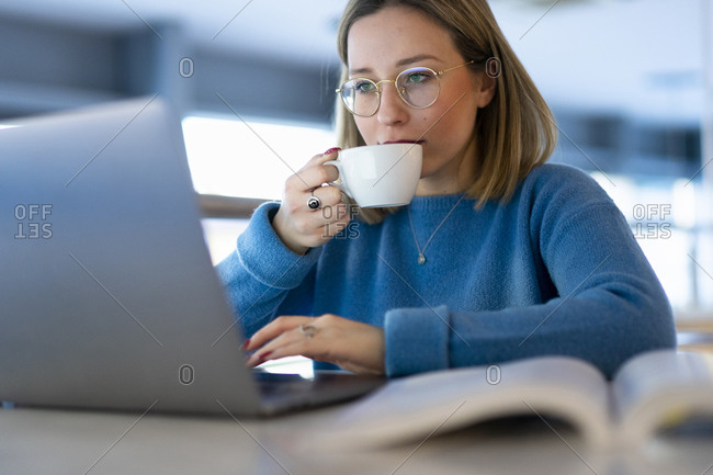 Female higher education student looking at laptop and drinking coffee in university cafe, close up