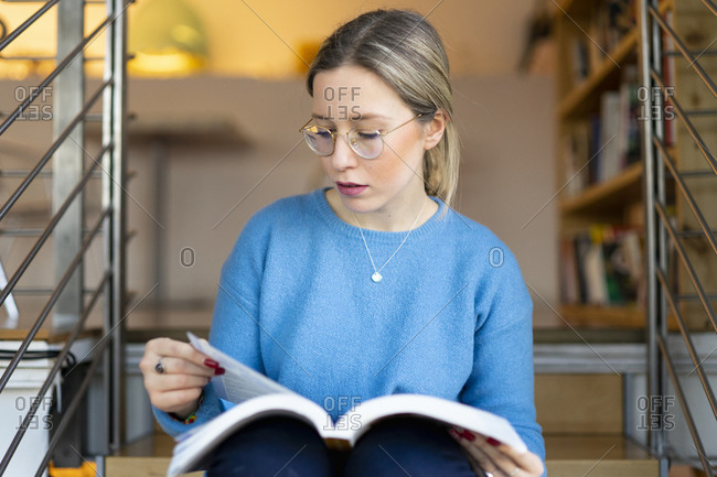 Female higher education student sitting on university stairway reading book