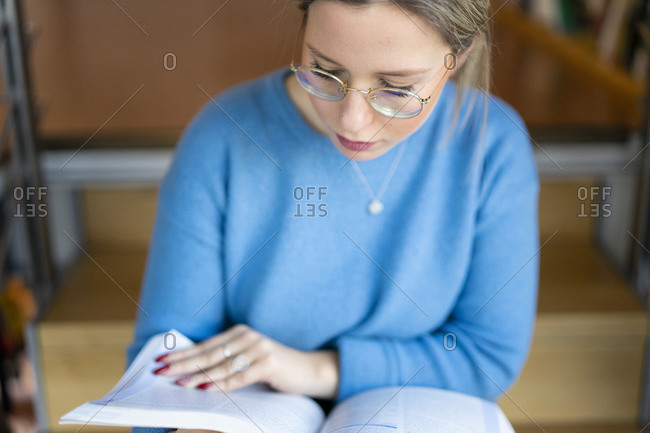 Female higher education student sitting on university stairway studying book