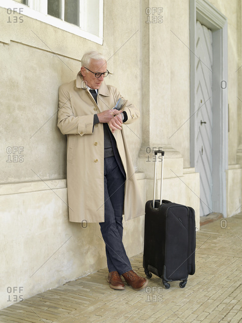 Senior man with wheeled suitcase leaning against building looking at his watch, Copenhagen, Hovedstaden, Denmark