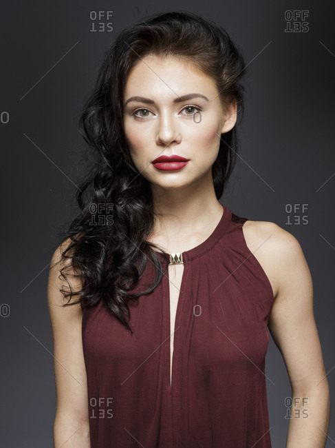 Beautiful young woman with long black hair, studio portrait