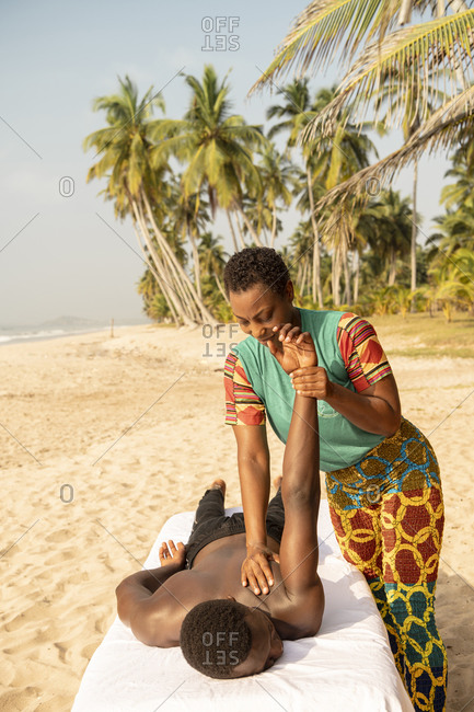 Woman massaging man on beach