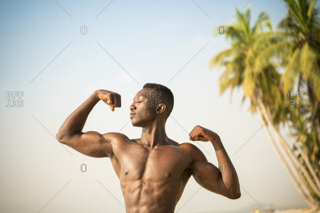 Man flexing arm muscles on beach