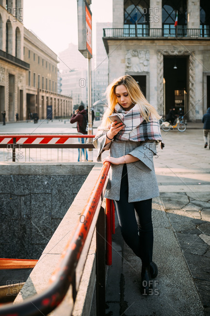 Young woman by underground station looking at smartphone, Milan, Italy