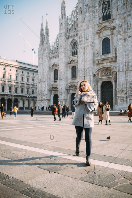 Young female tourist making smartphone call by Milan Cathedral, Milan, Italy
