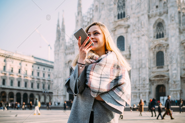 Young female tourist talking at smartphone by Milan Cathedral, Milan, Italy