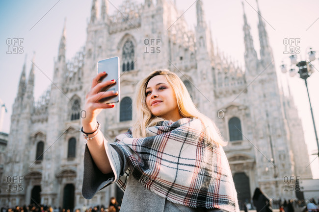 Young female tourist taking smartphone selfie in front of Milan cathedral, Milan, Italy