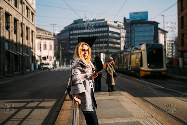 Young female tourist waiting at tram station, Milan, Italy