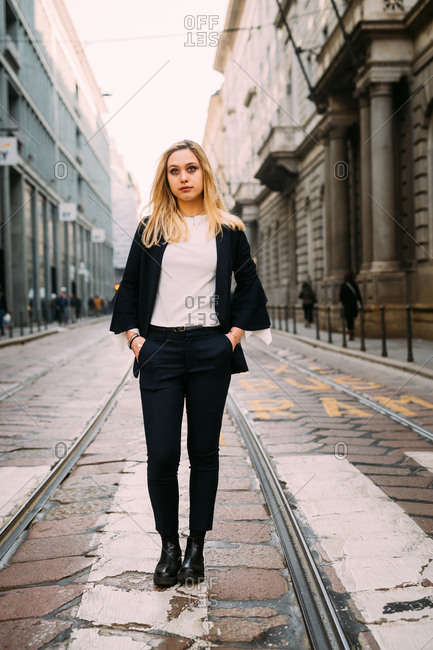 Young woman standing on pelican crossing, Milan, Italy