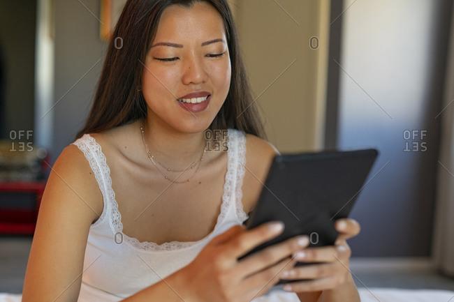 Woman using digital tablet in room