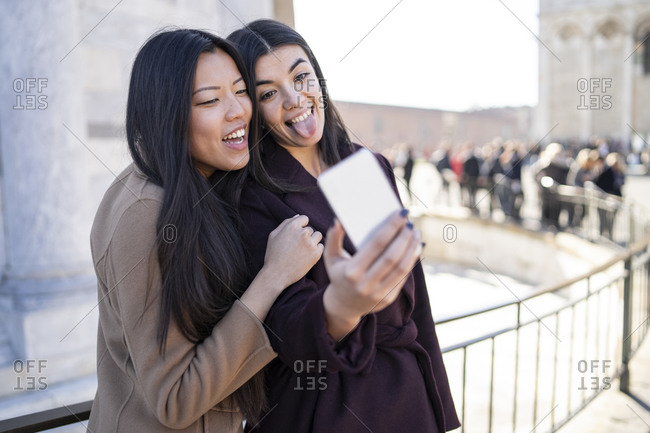 Friends taking selfie and sticking out tongue at smartphone, Pisa, Toscana, Italy