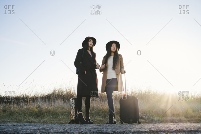 Friends waiting with wheeled luggage on roadside