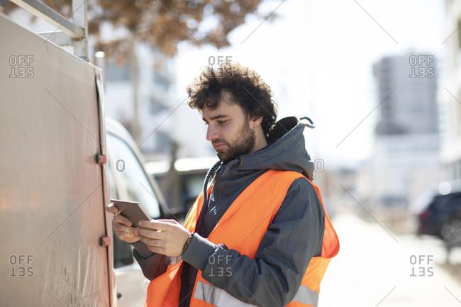 Man using digital tablet on street