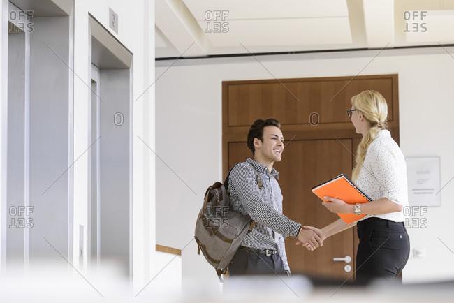 Colleagues shaking hands in corridor