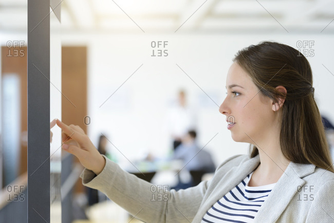 Businesswoman pointing at drawing on board