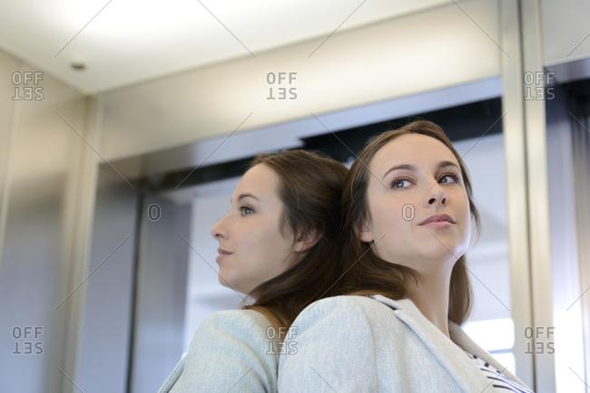 Caucasian businesswoman daydreaming inside elevator
