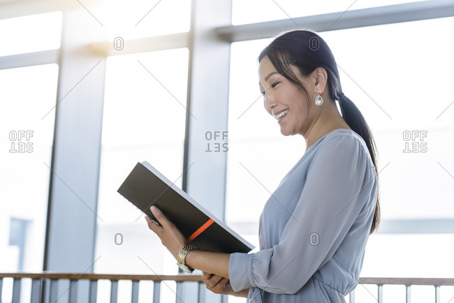 Businesswoman reading business plan in office