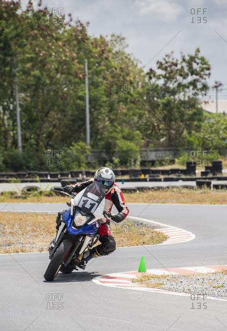 Male motorcyclist riding motorbike around bend on race track,  Bangkok