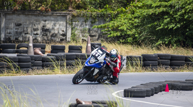 Male motorcyclist riding motorbike leaning sideways around hairpin bend on race track,  Bangkok