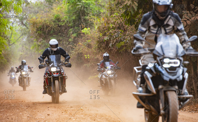 Male friends riding ADV motorcycles on dusty rural road in Cambodia, rear view