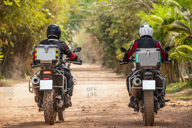Two male friends riding ADV motorcycles on rural road in Cambodia, rear view