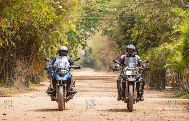 Two male friends riding ADV motorcycles on rural road in Cambodia