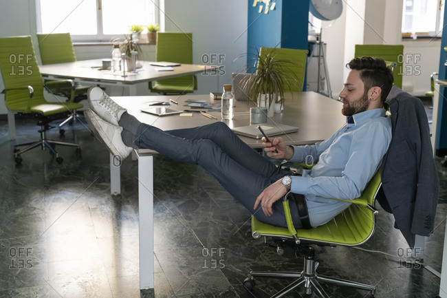 Young male business creative with feet up looking at smartphone in office