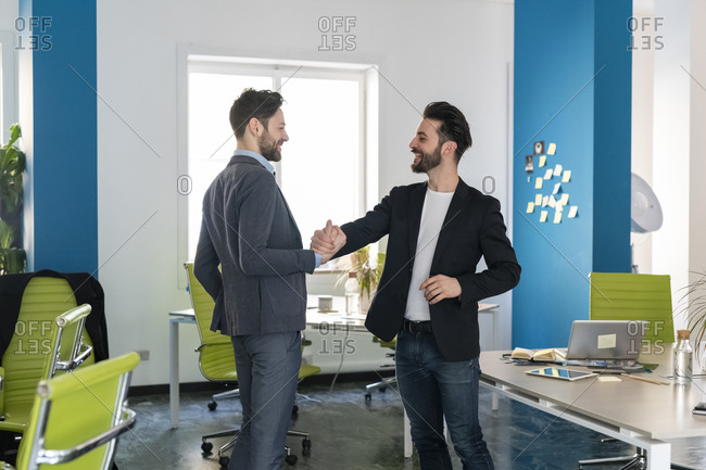 Two male business creatives smiling and shaking hands in office