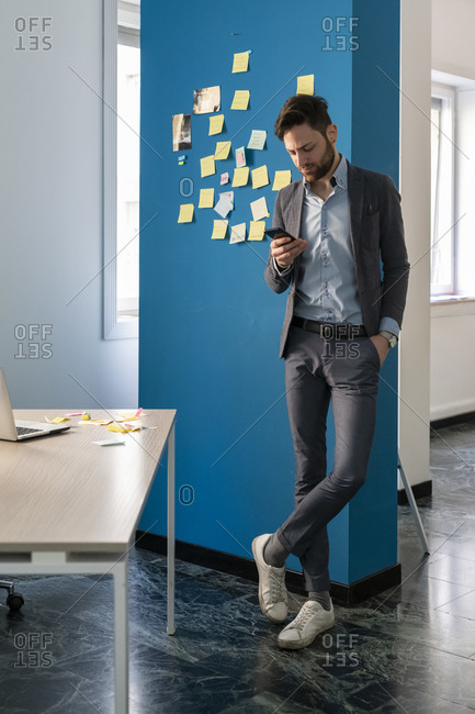 Young male business creative looking at smartphone in open plan office