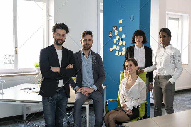 Young male and female business creative team in open plan office, portrait