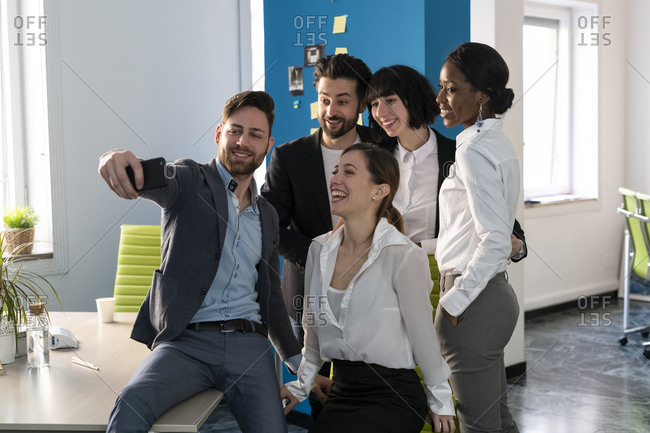 Young male and female business creative team taking smartphone selfie in open plan office