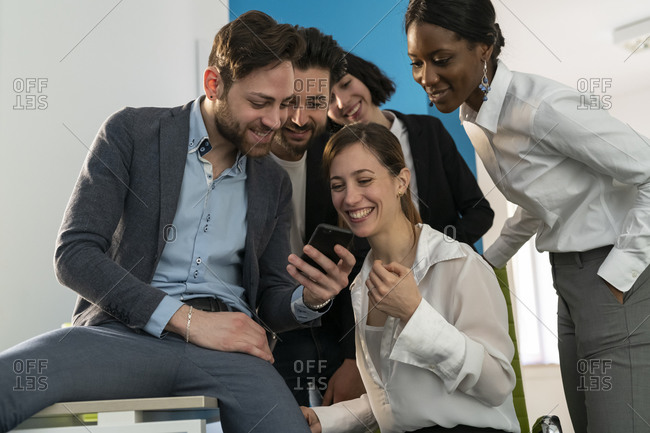 Young female and male business creative team looking at smartphone in office
