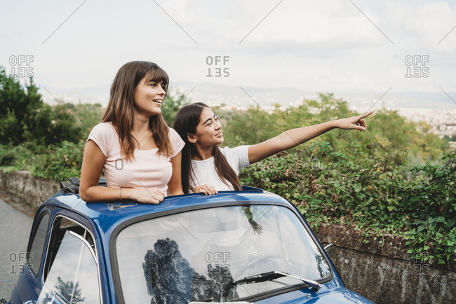 Friends enjoying view in car sunroof, Florence, Toscana, Italy
