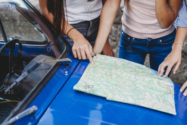 Friends reading route map on car bonnet
