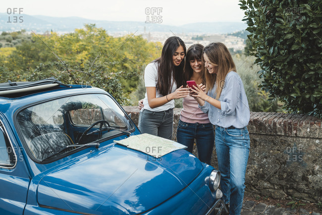 Friends using smartphone in countryside, Florence, Toscana, Italy