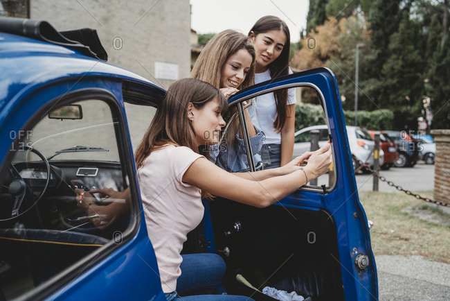 Friends using smartphone beside car