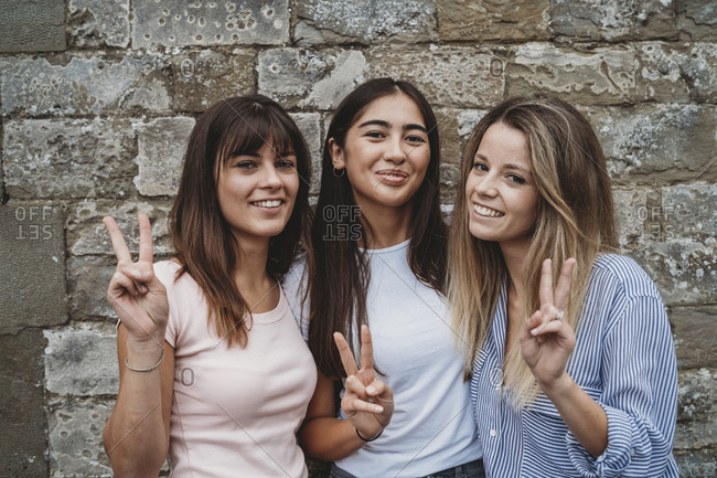 Portrait of friends gesturing peace sign against stonewall