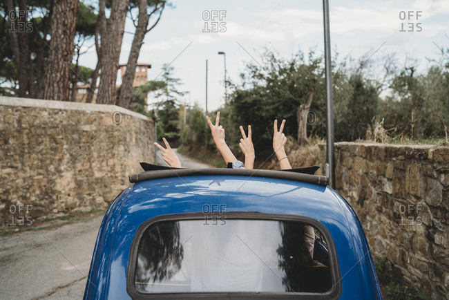 Friends gesturing peace sign in car sunroof, Florence, Toscana, Italy