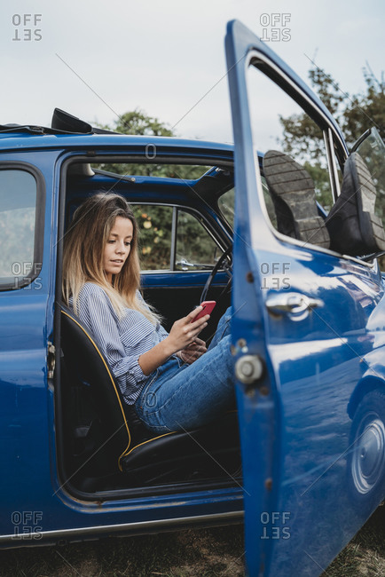 Woman using smartphone inside car