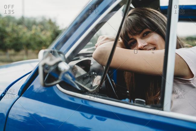Woman leaning against steering wheel