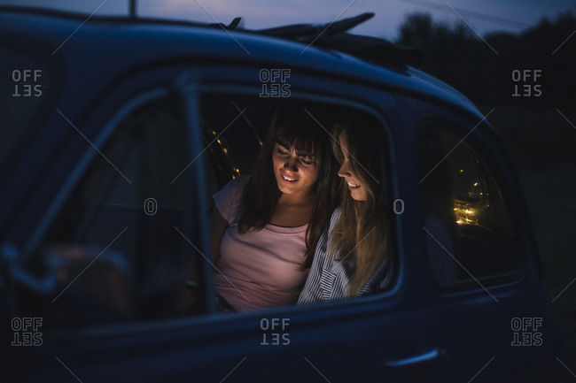 Friends using smartphone inside car
